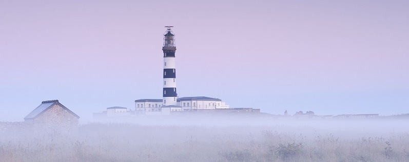 Vue sur le phare du Creac'h, a l'aube et dans la brume.